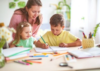 mother daughter and son draws pencil on a sheet of paper sitting at home at table in a bright room.positive emotions from the process of drawing a smile and happiness.mother enjoys the child's success