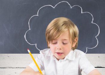 Attentive schoolboy doing homework against blackboard